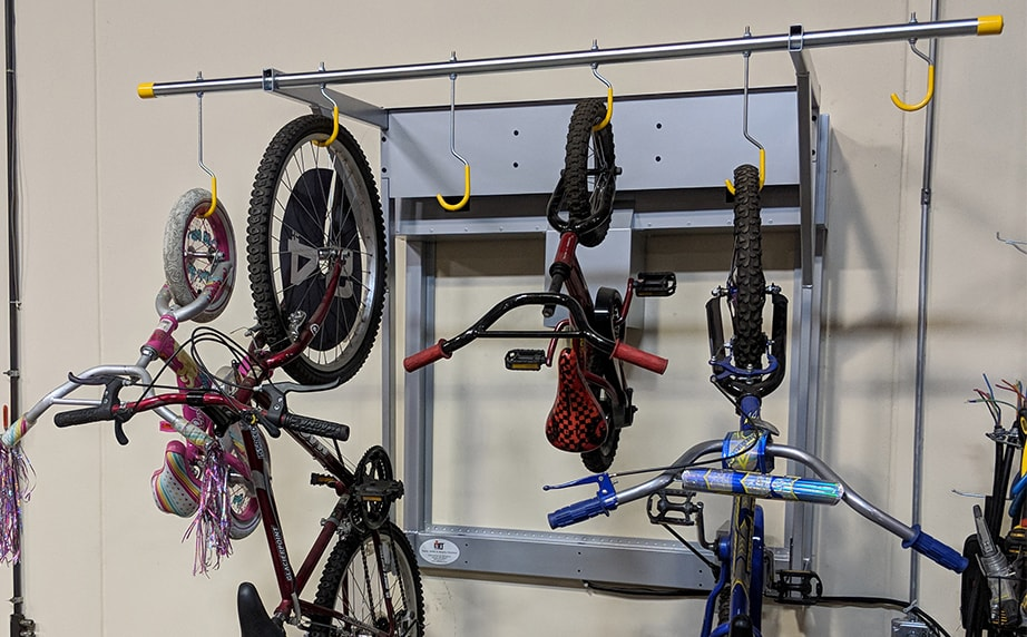close up of multiple bicycles hanging on new tilt n store wall mount