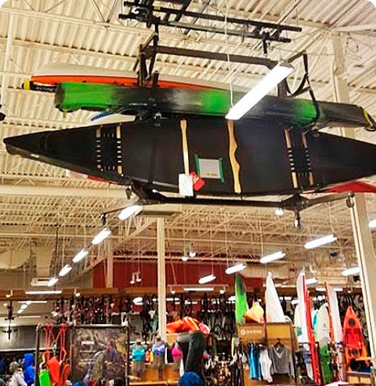 kayaks hanging from rack inside of store