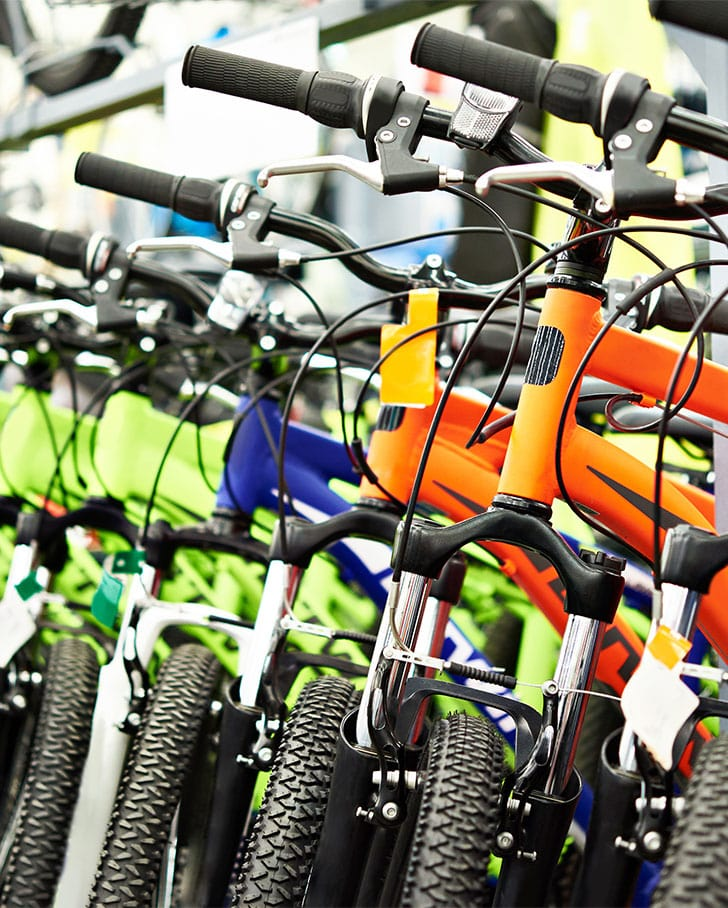 row of bicycles lined up inside of store