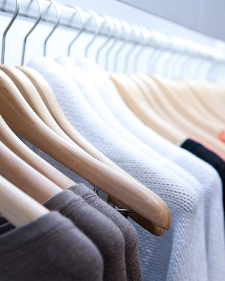 close up of an organized clothing rack using overhead storage solutions